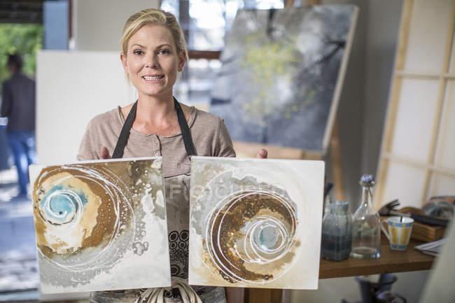 Frau hält Kunstwerke im heimischen Atelier — Stockfoto