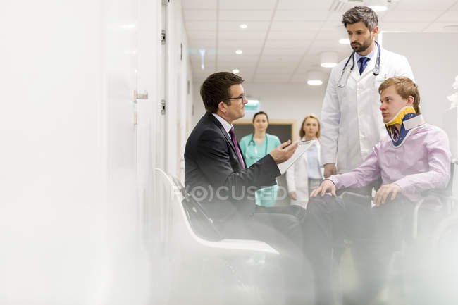 Doctor, man in suit and patient in wheelchair talking on hospital floor — Stock Photo