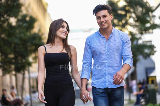 Felice giovane coppia a piedi mano nella mano — Foto stock