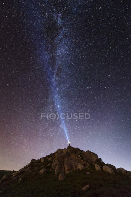 Spain, man illuminating the sky on a starry night with blue ray — Stock Photo