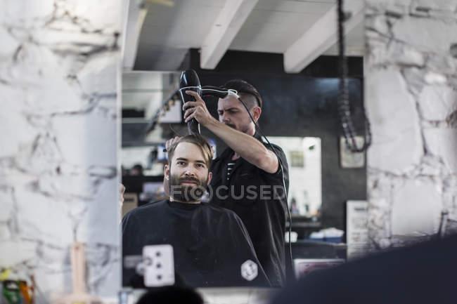 Barber blow-drying hair of a customer at barbershop — Stock Photo