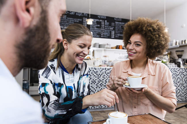 Three friends meeting in a cafe — Stock Photo