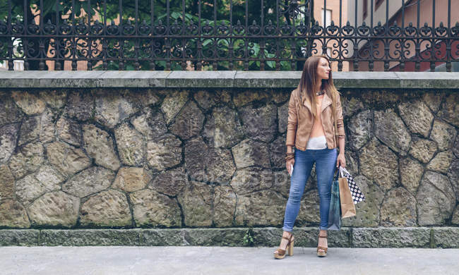 Donna che tiene borse della spesa in piedi davanti al muro di pietra — Foto stock