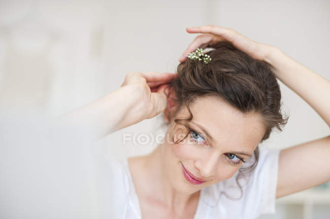 Close-up of Woman putting flowers in hair — Stock Photo
