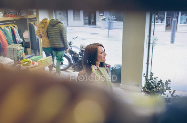 Smiling woman shopping for clothes in a boutique — Stock Photo