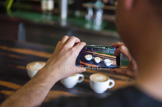 Homem tirando foto de celular de xícaras de cappuccino — Fotografia de Stock
