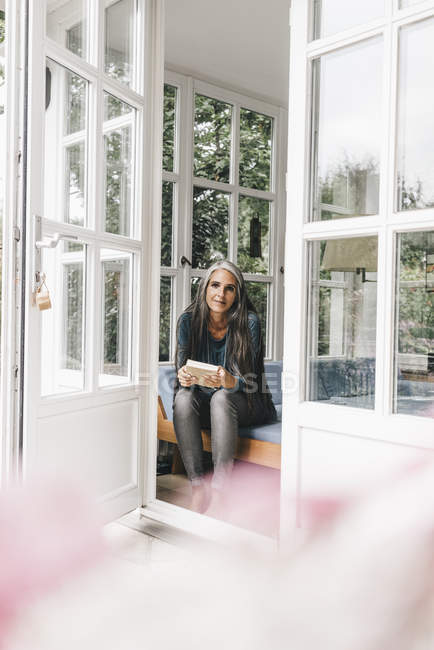 Donna sorridente con libro seduta sulla lounge — Foto stock