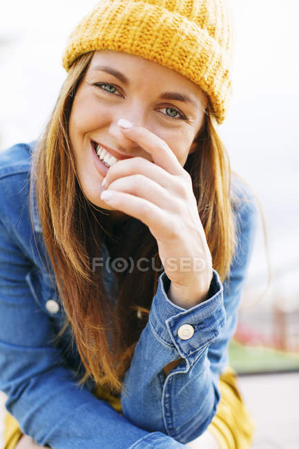 Portrait of laughing young woman wearing yellow cap — Stock Photo