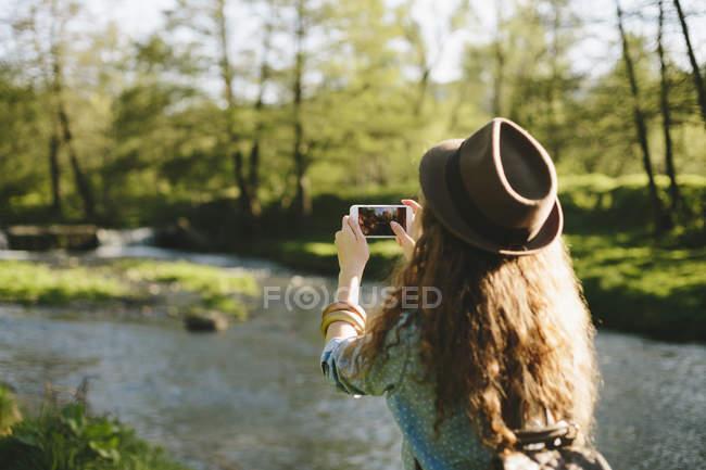 Vue arrière du portrait de prendre femme voung avec smartphone — Photo de stock