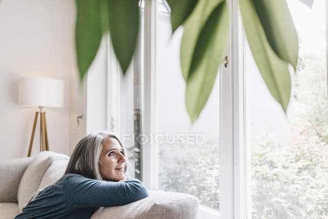 Woman relaxing on couch at home — Stock Photo
