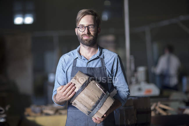 Cooper holding wine barrel in storage and looking at camera — Stock Photo