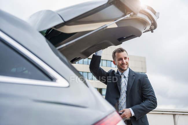 Uomo d'affari al bagagliaio auto — Foto stock