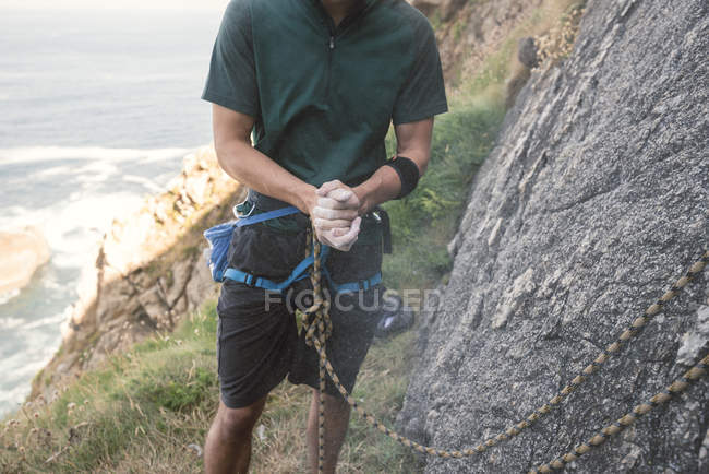 Climber applying magnesium in hands next to rock — Stock Photo