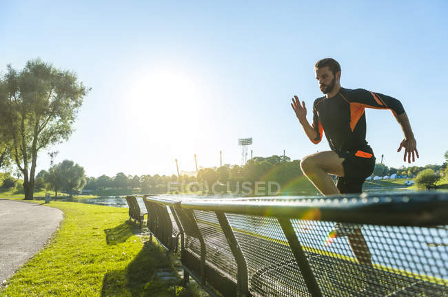 Male athlete jumping over bench at riverside — Stock Photo