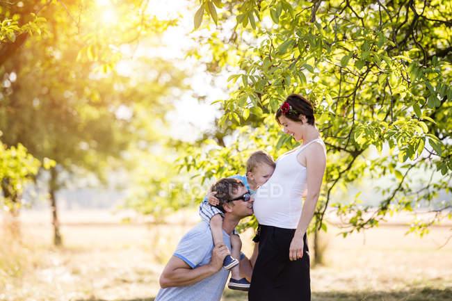 Vater und Sohn küssen Schwangeren Bauch im Freien, Sonne in Bäumen im Hintergrund — Stockfoto