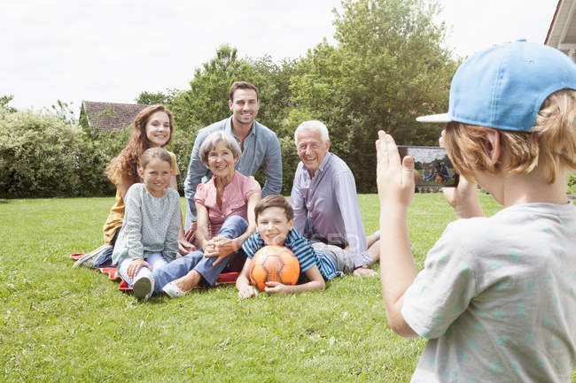 Boy taking picture of happy extended family in garden — Stock Photo