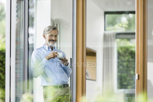 Homem sorridente com copo de pé de café em sua casa, olhando pela janela — Fotografia de Stock