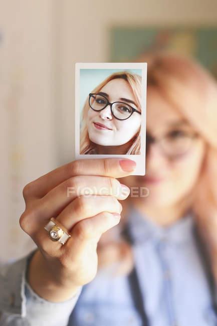 Jovem segurando uma foto de si mesma — Fotografia de Stock