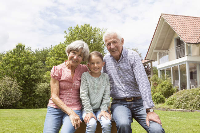 Portrait of happy grandparents with granddaughter in garden — Stock Photo