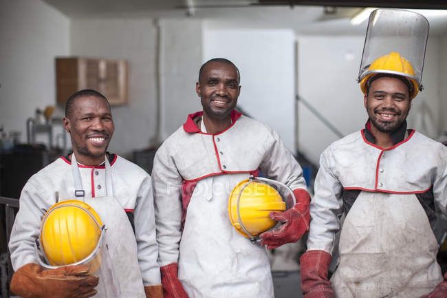 Portrait of three smiling workers with safety helmets — Stock Photo