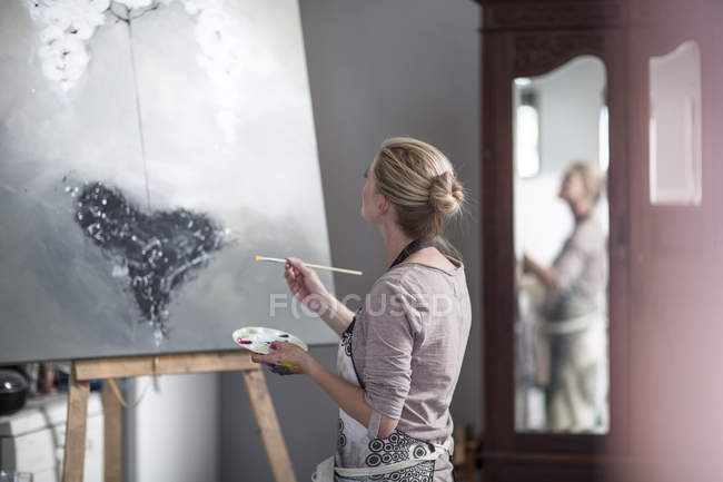 Female painter painting on canvas — Stock Photo
