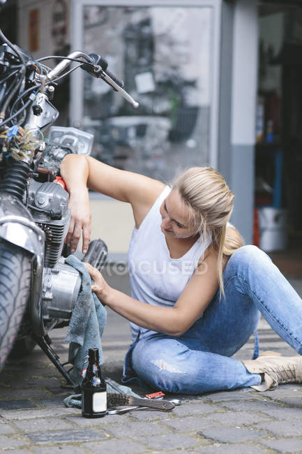 Woman cleaning motorbike — Stock Photo