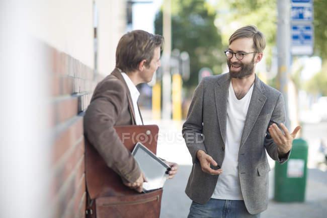 Двое мужчин, говорят в городе — стоковое фото