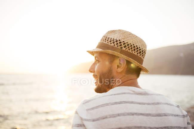 Grèce, Îles Cylcades, Amorgos, homme profitant du coucher de soleil au bord de la mer — Photo de stock