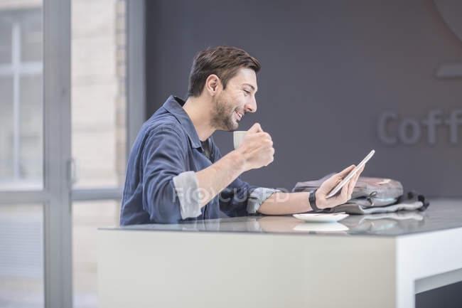 Homme souriant utilisant une tablette numérique au bureau — Photo de stock