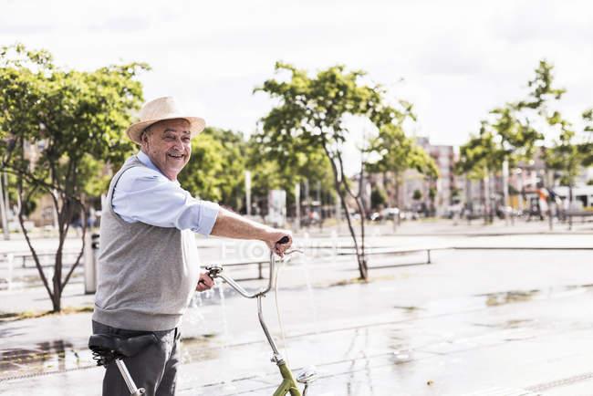 Smiling senior man with folding bicycle — Stock Photo