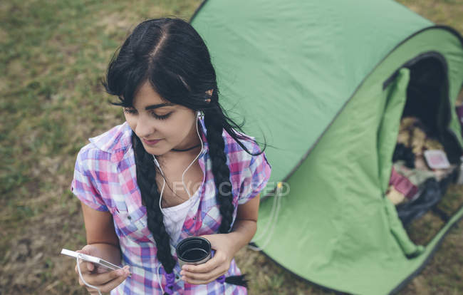 Young woman in front of a tent with cup of coffee listening music with earphones — Stock Photo