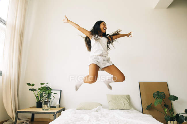 Woman jumping on bed — Stock Photo