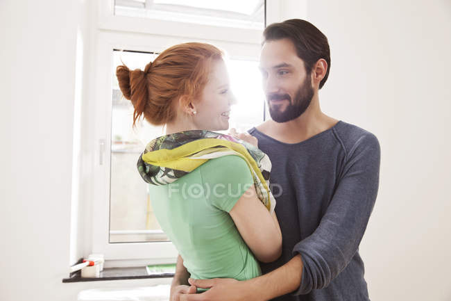 Happy young couple hugging in white room — Stock Photo