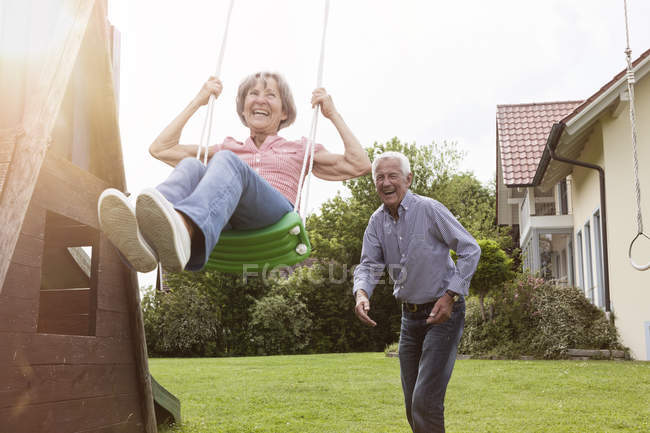 Playful senior couple with swing in garden — Stock Photo