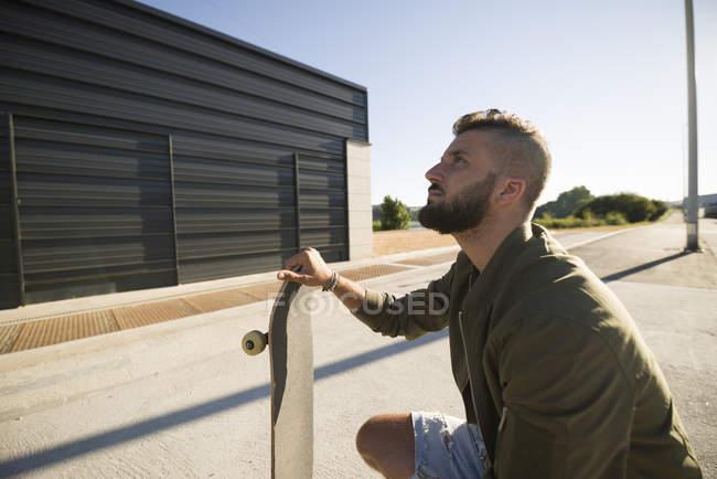 Uomo seduto con skateboard — Foto stock