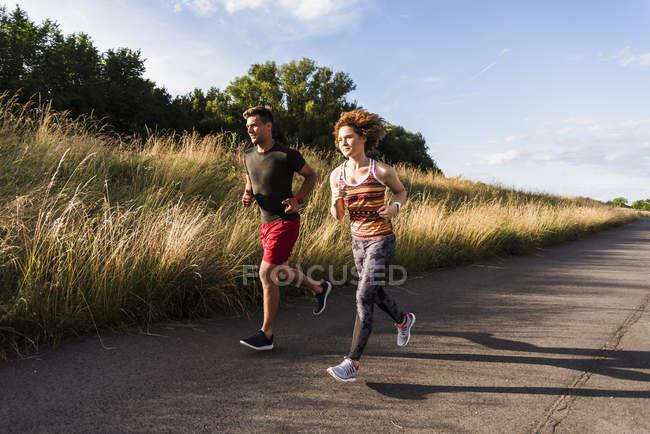 Пара бегущих по проселочной дороге — стоковое фото