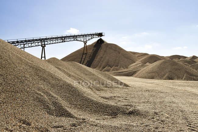 Conveyor belt above heap of gravel — Stock Photo