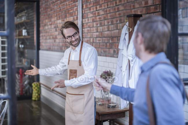 Man welcoming customer — Stock Photo