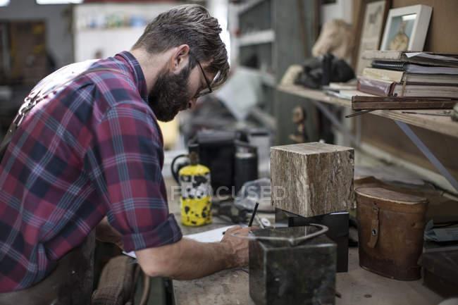 Бородач в мастерской рисунок, вид сбоку — стоковое фото