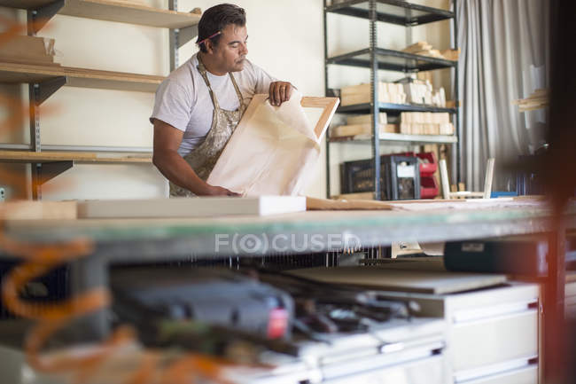Man looking at wooden frame for canvas preparation in workshop — Stock Photo