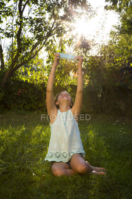 Girl sitting on meadow and taking selfie with tablet — Stock Photo
