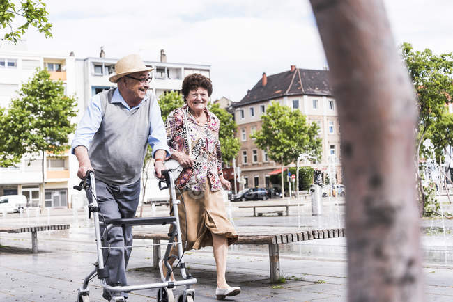Senior couple strolling with wheeled walker — Stock Photo