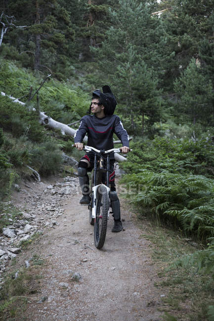 Mountainbiker on forest path having a break — Stock Photo