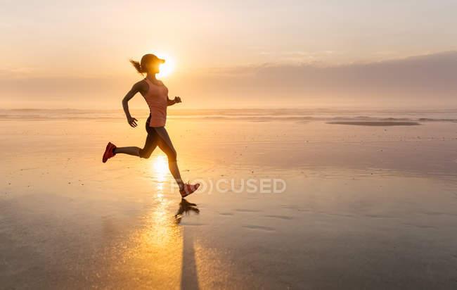 Mulher correndo na praia ao pôr do sol — Fotografia de Stock
