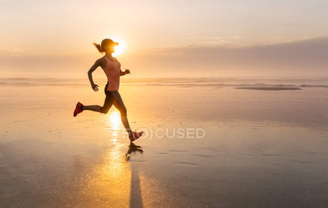 Woman running on the beach at sunset — Stock Photo