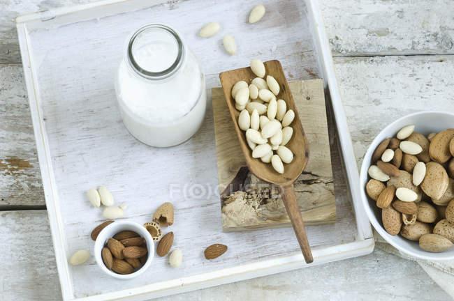 Стеклянная бутылка домашнего миндального молока, цельного и треснутого миндаля — стоковое фото