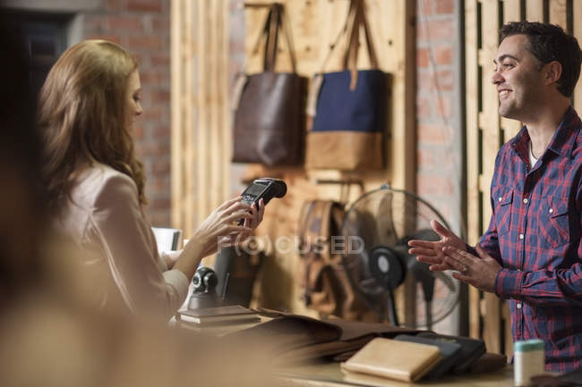 Woman paying with credit card in leather goods shop — Stock Photo
