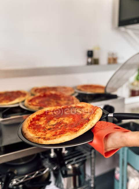 Closeup of chief preparing homemade pizzas at kitchen — Stock Photo