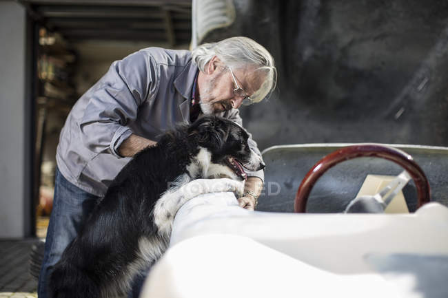 Людина з собакою, вивчаючи автомобіля — стокове фото
