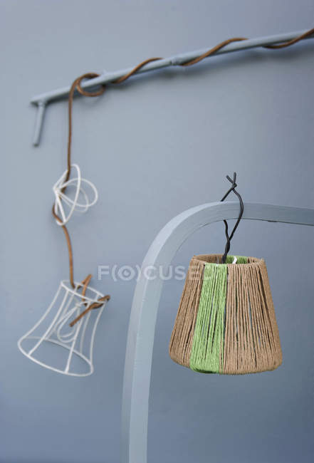 Upcycled lampshades hanging on planks indoors — Stock Photo